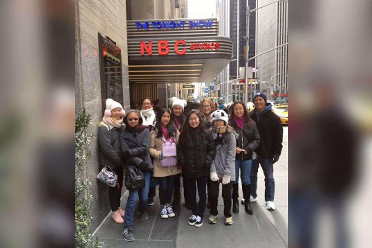 Group of 10 teens and adults wearing heavy coats in front of neon sign (The Tonight Show/NBC Studios)