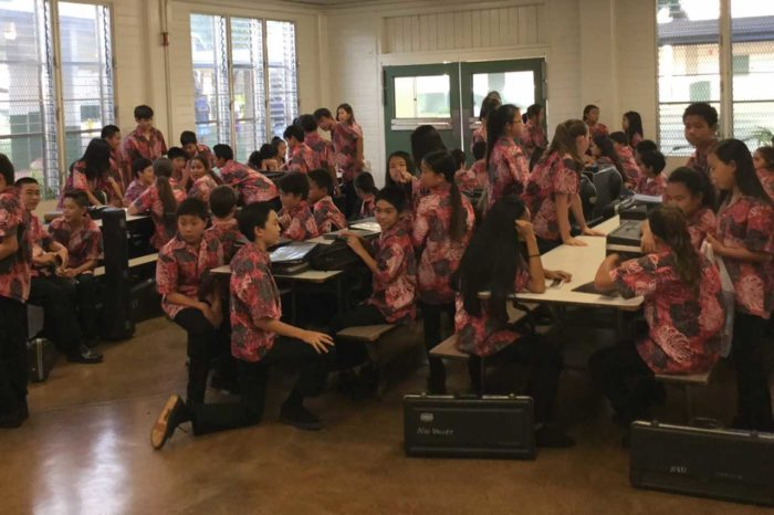 About 30 band students in red, black and white aloha shirts and black pants sit at cafeteria tables with black instrument cases on the brown floor.