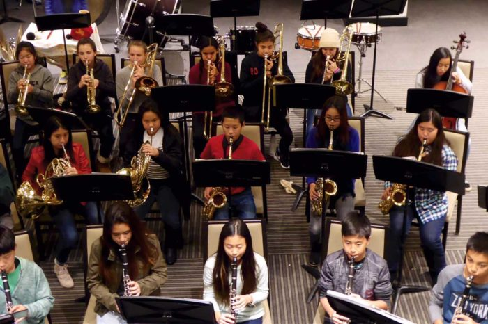 Three rows of students playing clarinet, French horn, saxophone, trumpet, and trombone