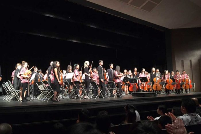 Orchestra students stand at their seats on stage after playing a concert