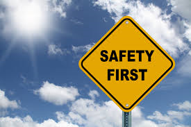 Yellow diamond shaped Safety First sign with blue sky and clouds in the background