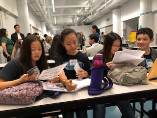Four students sitting with bags and water bottle on table