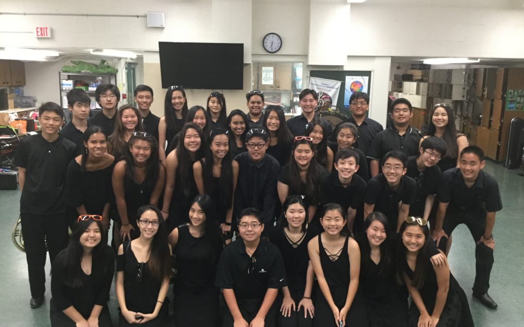 group of 40 students dressed in black in bandroom