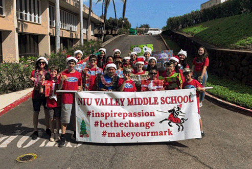 Group of students wearing red standing in roadway and holding Niu Valley Middle School parade banner