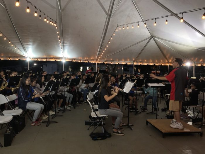 Group of band students rehearsing under a tent with lights