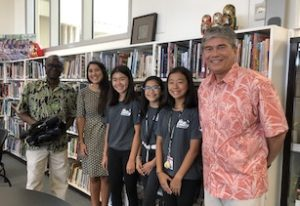Camera man, teacher, three girls, and man in aloha shirt stand in front of books in library