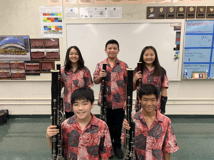 Five band students in red aloha uniform shirts and black pants each holding a bassoon