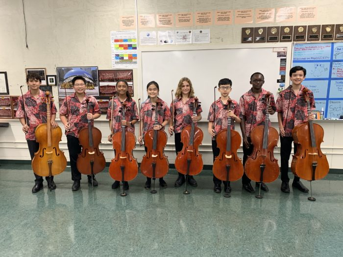 Eight orchestra students in red aloha uniform shirts and black pants each holding a cello