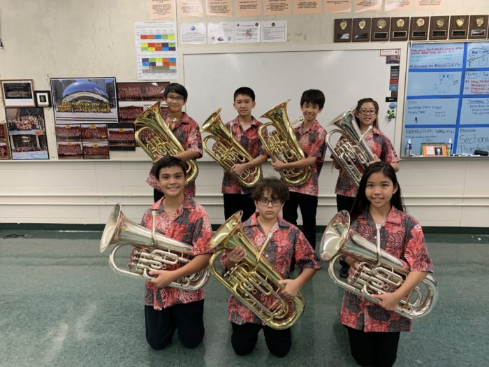 Seven band students in red aloha uniform shirts and black pants each holding a euphonium