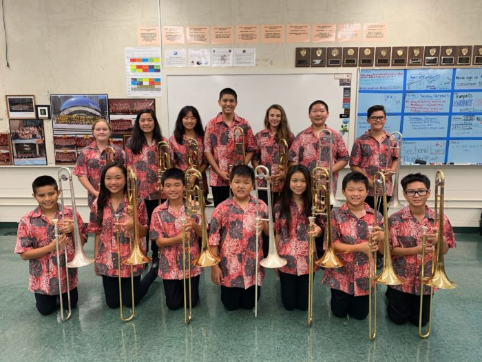 Two rows of band students in red aloha uniform shirts and black pants holding a trombone