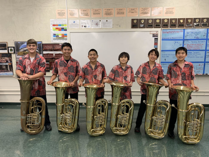 Six band students in red aloha uniform shirts and black pants each in back of a tuba