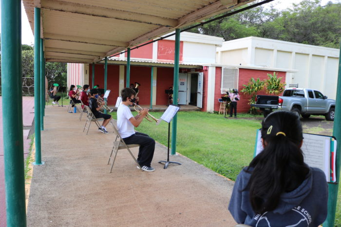 Students playing trumpets outdoors while wearing face masks sitting 6 feet apart