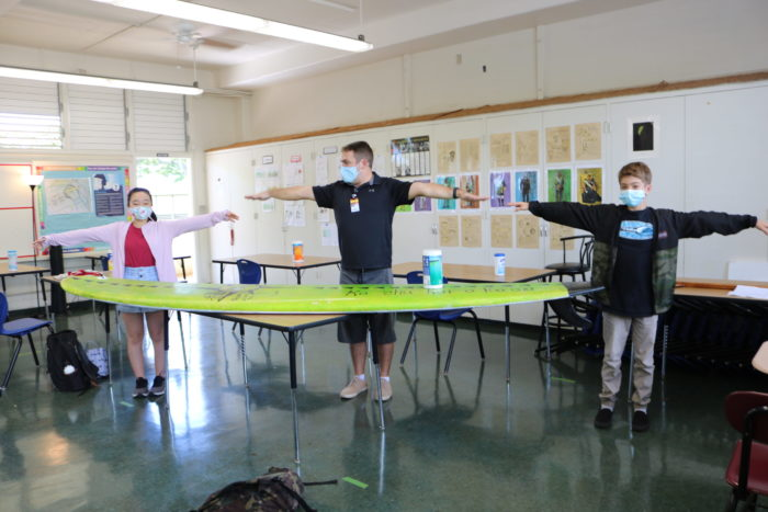 Teacher and students standing 6 feet apart using a surfboard as a visual example